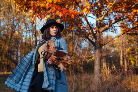 Autumn fashion. Young woman walking in forest wearing stylish outfit and holding purse. Clothing and accessories