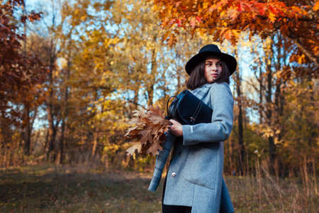 Autumn fashion. Young woman walking in park wearing stylish outfit and holding purse. Clothing and accessories