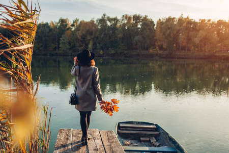Woman walking on lake pier by boat admiring autumn landscape. Fall season activities 스톡 콘텐츠