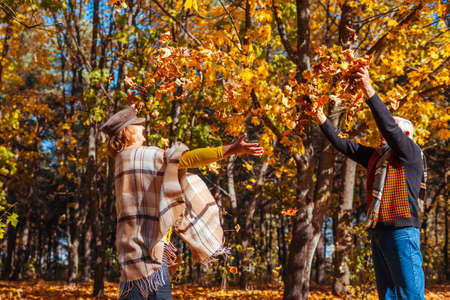 Fall season. Couple throwing leaves in autumn forest. Senior family having fun outdoors playing games