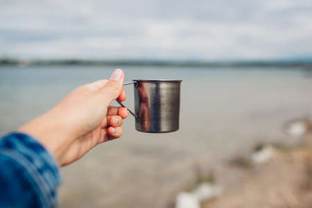 Woman tourist drinking hot tea by summer lake. Girl holding metal cup. Camping, traveling and sport concept Archivio Fotografico