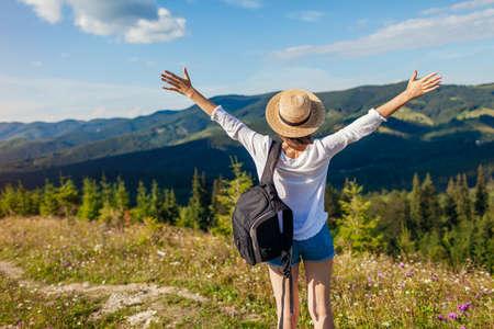 Trip to Carpathian mountains. Happy woman tourist hiking and raising arms feeling free enjoying landscape. Traveling in summer Ukraine Archivio Fotografico