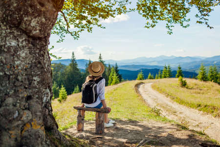 Trip to Carpathian mountains. Woman tourist hiking and relaxing admiring landscape sitting under tree with backpack. Traveling in summer Ukraine Archivio Fotografico