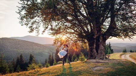Loving newlyweds couple hugging in mountains at sunset. Groom holding bride on hands under big tree. Wedding in summer Carpathians.