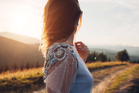 Beautiful bride wearing blue wedding dress in mountains at sunset. Young woman enjoys summer landscape. Close up of fashionable decor