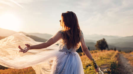 Beautiful bride dancing in blue wedding dress in mountains at sunset. Woman throws veil holding flowers. Wedding in Carpathians