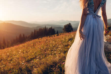 Beautiful bride wearing blue wedding dress in mountains at sunset. Young woman enjoys summer Carpathians landscape holding bouquet of flowers. Back view