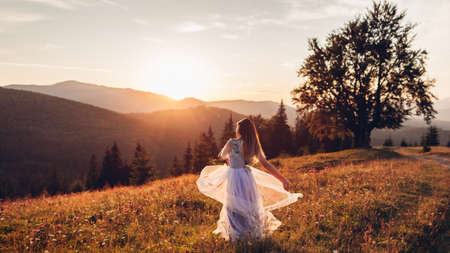 Beautiful bride dancing in blue wedding dress in Carpathian mountains at sunset. Woman enjoys landscape holding gown. Back view