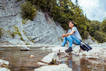 Young man tourist relaxing by mountain river enjoying natural landscape. Traveller backpacker sitting on rock. Summer trip