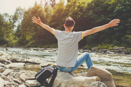 Man relaxing sitting on rock by mountain river enjoying natural landscape. Traveller backpacker raising arms feeling happy. Summer trip