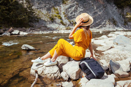 Portrait of young woman tourist relaxing by mountain river enjoying landscape. Traveller sitting on rock. Summer vacation