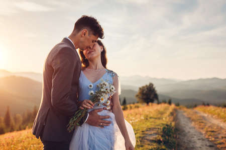 Young loving wedding couple hugging in mountains at sunset. Portrait of happy bride and groom in summer Carpathians. Archivio Fotografico