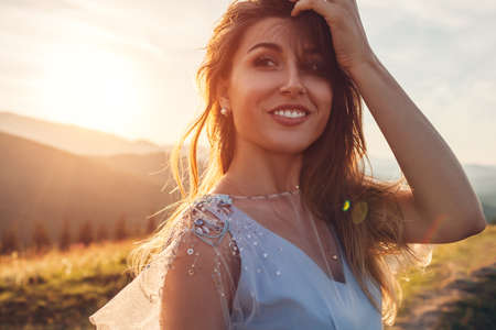 Beautiful bride wearing blue wedding dress in mountains at sunset. Happy young woman enjoys summer landscape. Close up portrait Archivio Fotografico