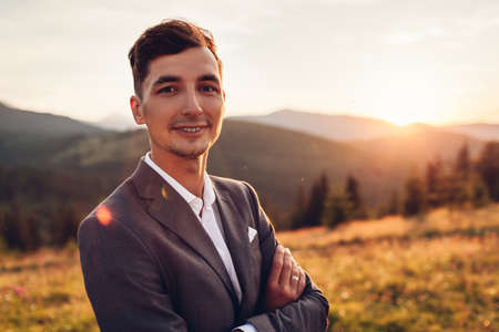 Handsome groom walking in wedding suit in Carpathian mountains at sunset. Smiling happy man enjoys landscape with hands crossed looking at camera