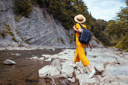 Young tourist woman hiking by mountain river enjoying landscape. Traveler walking with backpack along rocks. Summer vacation Archivio Fotografico