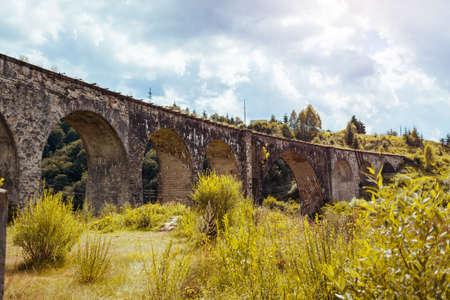 Viaduct railway bridge in Vorokhta. Ancient architecture landmark. Trip to Carpathian summer mountains in Ukraine. Traveling Archivio Fotografico