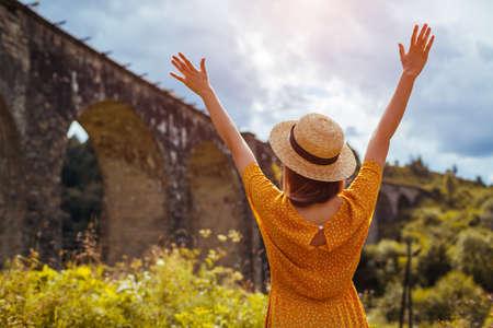 Tourist feeling happy enjoying view of viaduct railway bridge in Vorokhta. Trip to summer Carpathian mountains in Ukraine Archivio Fotografico