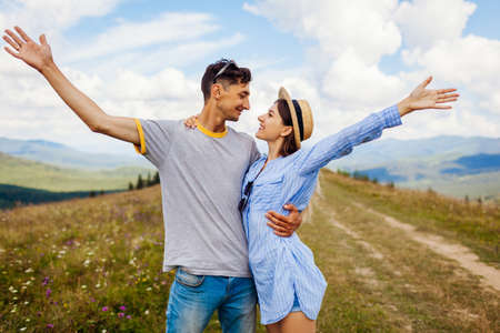 Loving couple of tourists raises arms feeling happy in Carpathian mountains enjoying view. Travelers have fun. Summer vacation