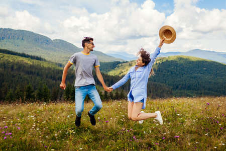Young loving couple of tourists jumps feeling happy in Carpathian mountains enjoying view. Travelers have fun. Summer vacation Archivio Fotografico