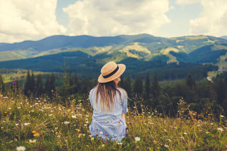 Traveling in summer Ukraine. Trip to Carpathian mountains. Young woman tourist sitting in flowers admiring view. Hiking