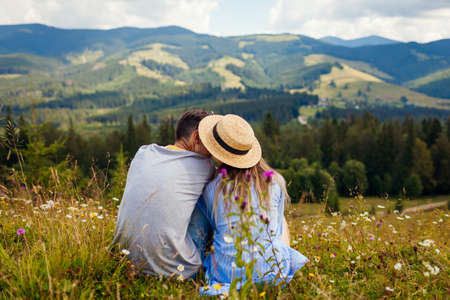 Couple of hikers relaxing sitting in Carpathian mountains enjoying landscape. Travelers kiss. Summer vacation. Back view