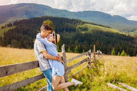 Couple of travelers walking by fence in Carpathian mountains enjoying landscape. People in love hug. Summer vacation