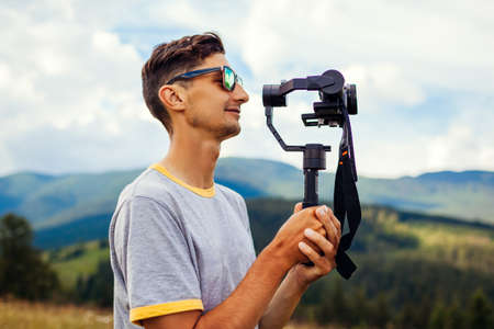 Videographer filming Carpathian mountains landscape. Man using steadicam and camera to make footage. Video shoot. Traveling wtih digital devices