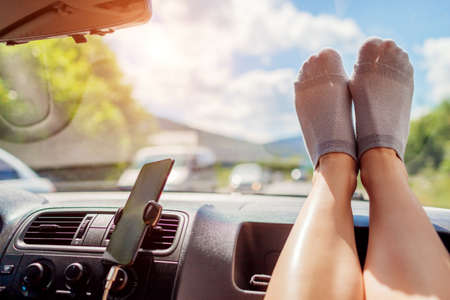 Woman put legs on car desk in salon. Passenger feels free and happy on road trip. Girl relaxes during ride having fun. Summer traveling