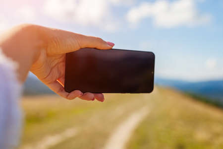 Woman hiker taking selfie with smartphone in mountains on hill peak. Close up of mobile phone screen. Saving memories. Space mockup Archivio Fotografico