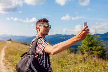 Man hiker taking selfie photo with smartphone in Carpathian mountains on hill peak. Traveler backpaker enjoys view of wild landscape Archivio Fotografico