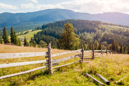 View of wooden fence in Carpathian mountains. Summer ukrainian landscape. Wild nature with forest on hills. Tourism