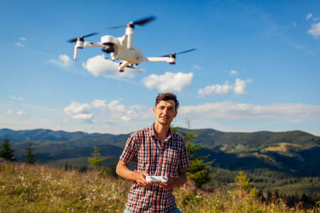 Drone remote control. Man operating copter controller in mountains. Aerial video shooting of summer Carpathins. Traveler uses new devices Archivio Fotografico