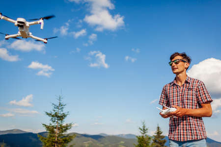 Aerial drone footage shooting of summer Carpathins. Man operating copter controller in mountains. Tourist filming wild nature