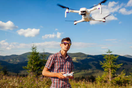 Man operating copter controller in mountains. Drone remote control. Aerial footage shooting of summer Carpathins. Tourist filming natural landscape Archivio Fotografico