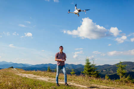 Drone video shooting of summer Carpathins. Man operating copter controller in mountains. Tourist filming wild nature
