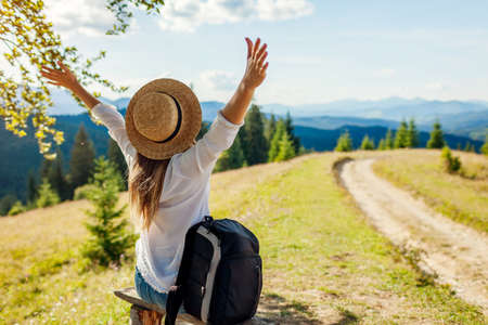 Trip to Carpathian mountains. Woman hiker relaxing admiring landscape with arms raised under tree with backpack. Traveling in summer Ukraine