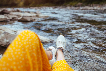 Woman relaxes by mountain river enjoying landscape. Traveler sitting on rock. Summer vacation. Close up of sport shoes Archivio Fotografico