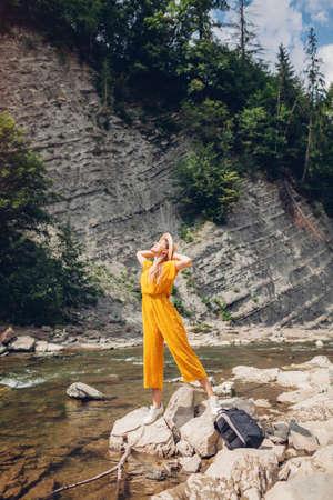 Woman tourist walking by mountain river enjoying landscape. Traveler feels happy. Summer vacation trip Archivio Fotografico