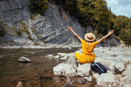 Hiker woman relaxing by mountain river enjoying landscape. Traveler raising arms sitting on rocks feeling happy. Summer vacation
