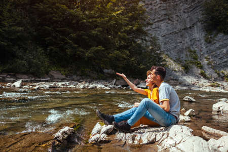 Couple of tourists have fun by mountain river enjoying landscape. Travelers sitting on rock splashing playing with water. Summer vacation