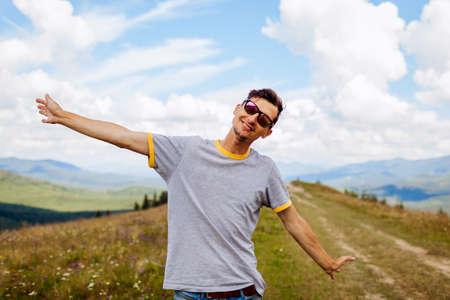 Happy man hiker raising arms feeling happy enjoying wild nature landscape. Traveling in summer Ukraine. Trip to Carpathian mountains. Archivio Fotografico