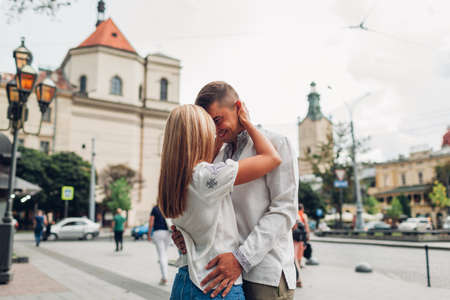 Young couple in love walking in old Lviv city wearing traditional ukrainian shirts. Man and woman hug and kiss outdoors