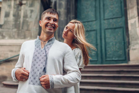 Man and woman in love walking in old Lviv city wearing traditional ukrainian shirts. Happy people hug by dominican cathedral