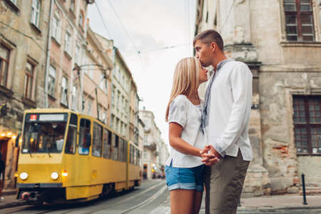 Boyfriend and girlfriend walking in old Lviv city wearing traditional ukrainian shirts. Couple hug on tram background surrounded with architecture
