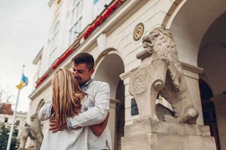 Happy couple in love walking in old Lviv city wearing traditional ukrainian shirts. Young people hug by town hall lion