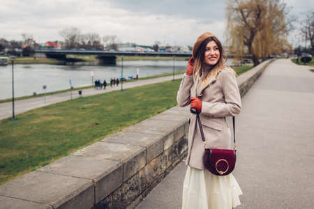 Stylish young woman tourist walking along pier by Wisla river in Krakow, Poland enjoying landscape. Europe autumn trip. Traveling