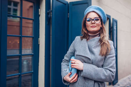Stylish woman wearing coat blue beret glasses and holding purse outdoors. Autumn fashionable female accessories. Trendy fall clothes. 免版税图像