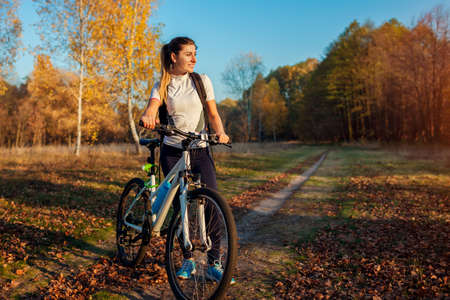 Riding bicycle in autumn forest. Young woman having rest after workout on bike enjoying nature. Healthy active lifestyle. Sport