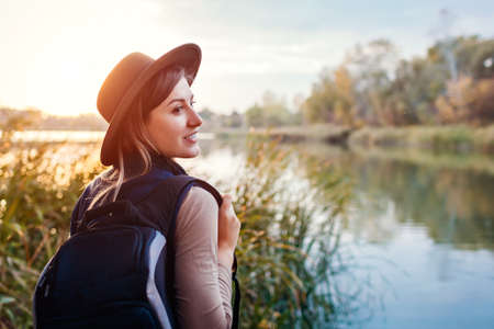 Traveler with backpack relaxing by autumn river at sunset. Happy young woman enjoys fall weather and landscape. Active lifestyle