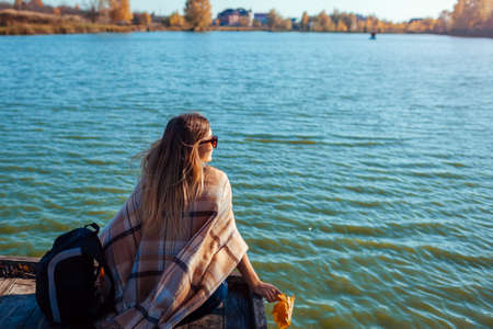 Traveler with backpack relaxing by autumn river at sunset. Young woman sitting on pier admiring landscape. Active lifestyle